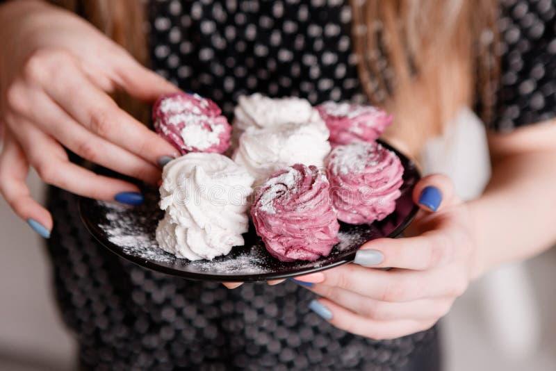 La giovane donna mangia gli zefiri dolci variopinti fotografia stock libera da diritti