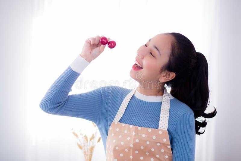 La giovane donna mangia l'uva fresca in cucina a casa immagine stock libera da diritti