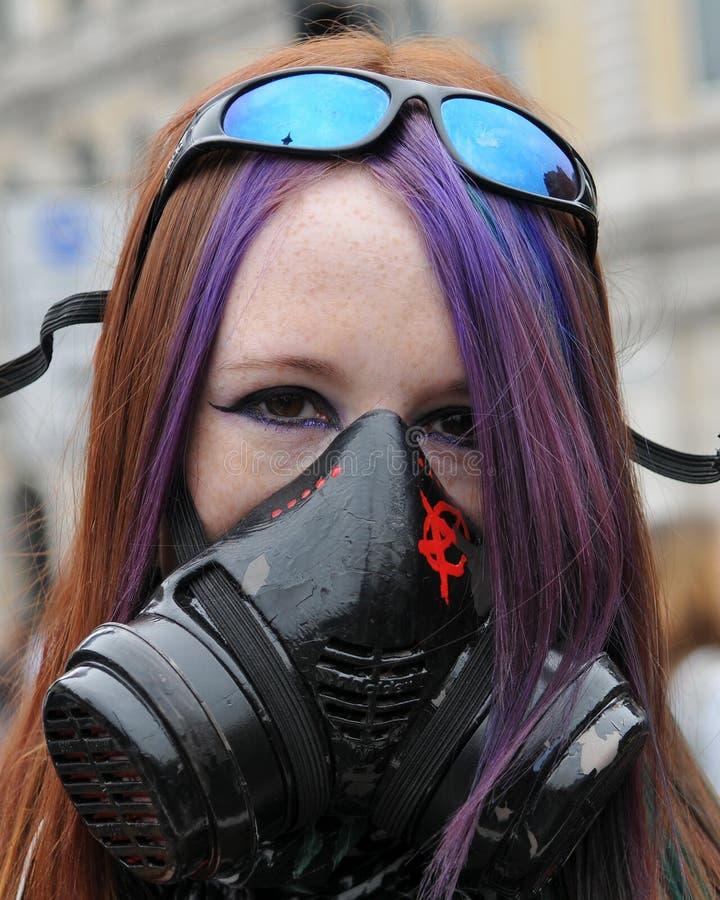La giovane donna mascherata all'Anti-Ha tagliato la protesta fotografia stock