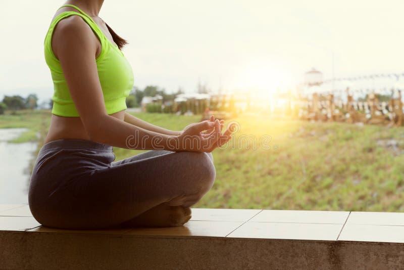 la giovane donna medita mentre pratica l'yoga all'aperto in parco, con riferimento a immagini stock libere da diritti