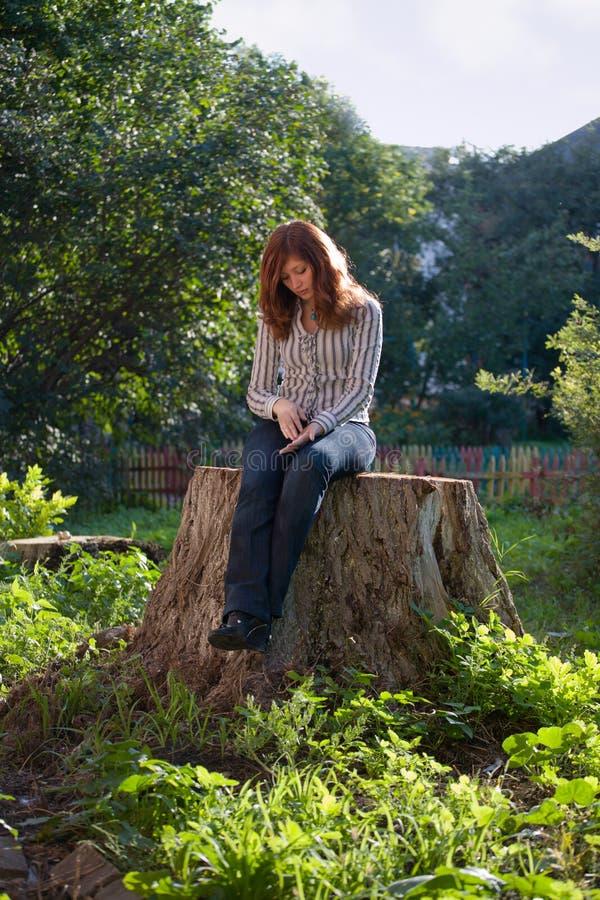 La giovane donna melancholic triste si siede sul grande albero mozzo immagini stock