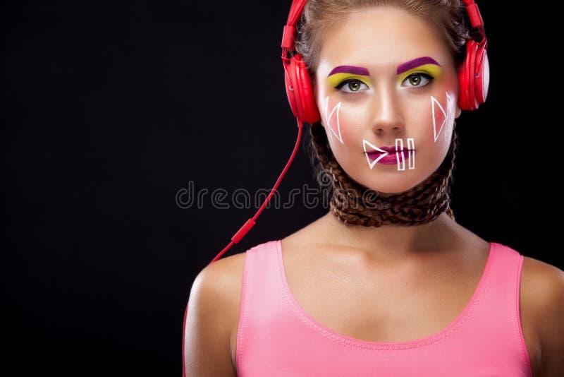 La giovane donna moderna con trucco di arte gode di di ascoltare la musica in cuffie Emozioni positive, svago Copi lo spazio fotografia stock