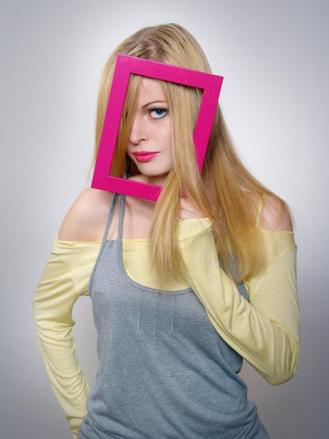 La giovane donna mostra i capelli biondi attraverso un blocco per grafici fotografia stock