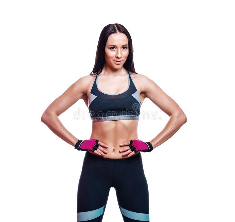 La giovane donna muscolare sportiva abbastanza caucasica su bianco ha isolato il fondo Ragazza del culturista o istruttore atleti fotografia stock