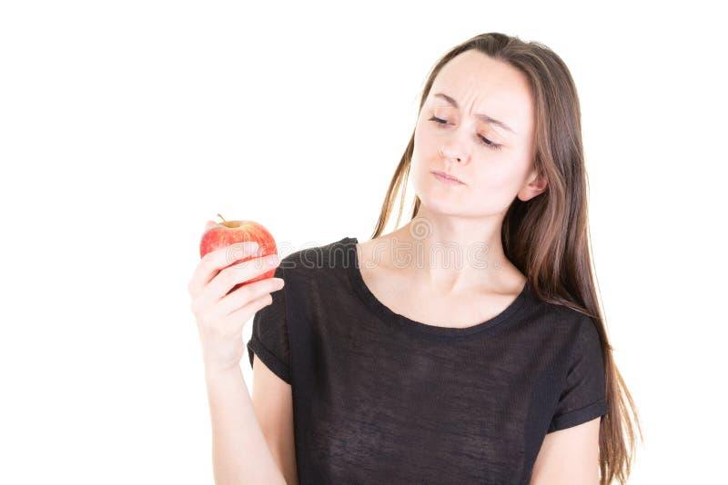 La giovane donna nel fondo bianco ha dubbio che mangia la mela rossa con il pensiero serio del fronte confuso immagine stock libera da diritti