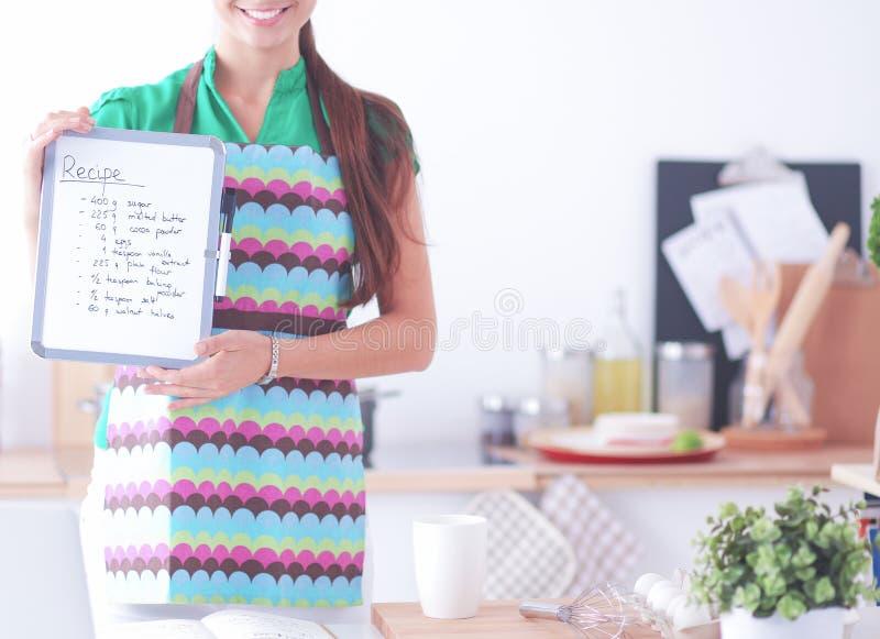 La giovane donna nel grembiule sta cucinando nella cucina fotografia stock