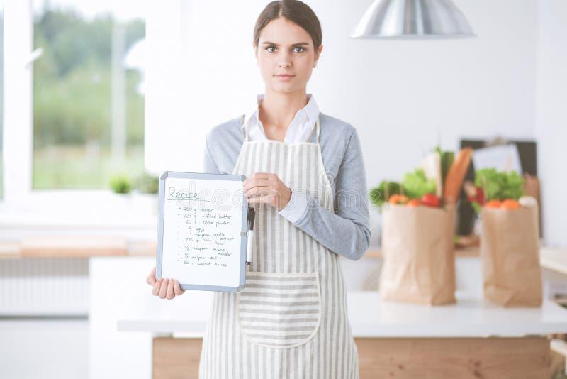 La giovane donna nel grembiule sta cucinando nella cucina immagini stock