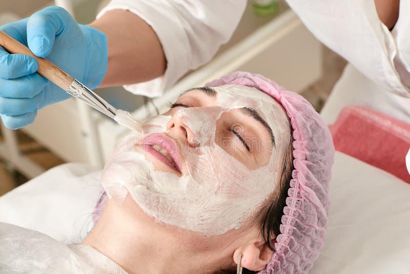 La giovane donna nel salone di bellezza fa la domanda di idratazione, ammorbidendo, rigenerante la maschera fotografia stock