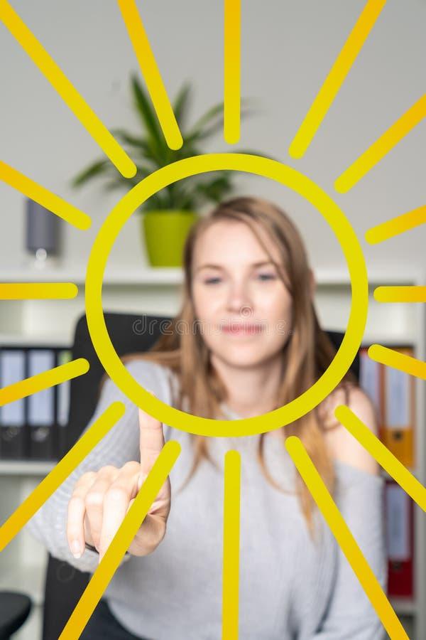 La giovane donna nell'ufficio dipinge un sole con il suo dito fotografie stock