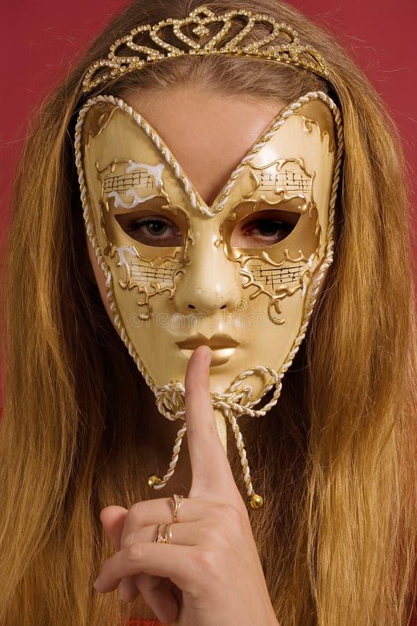 La giovane donna nella mascherina mostra il gesto di silenzio fotografia stock libera da diritti