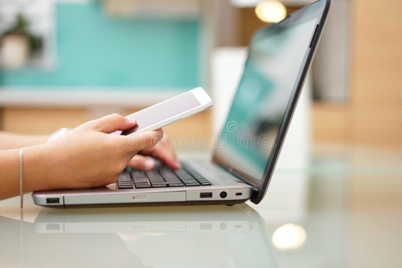 La giovane donna occupata sta scrivendo sul computer portatile e sta usando il cellulare p fotografia stock