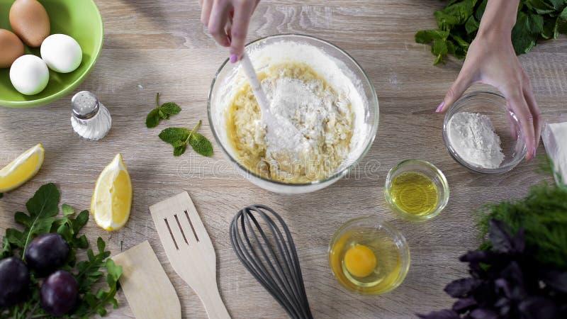 La giovane donna passa produrre la pasta in ciotola di vetro, mescolante i prodotti di cottura per pizza immagini stock libere da diritti