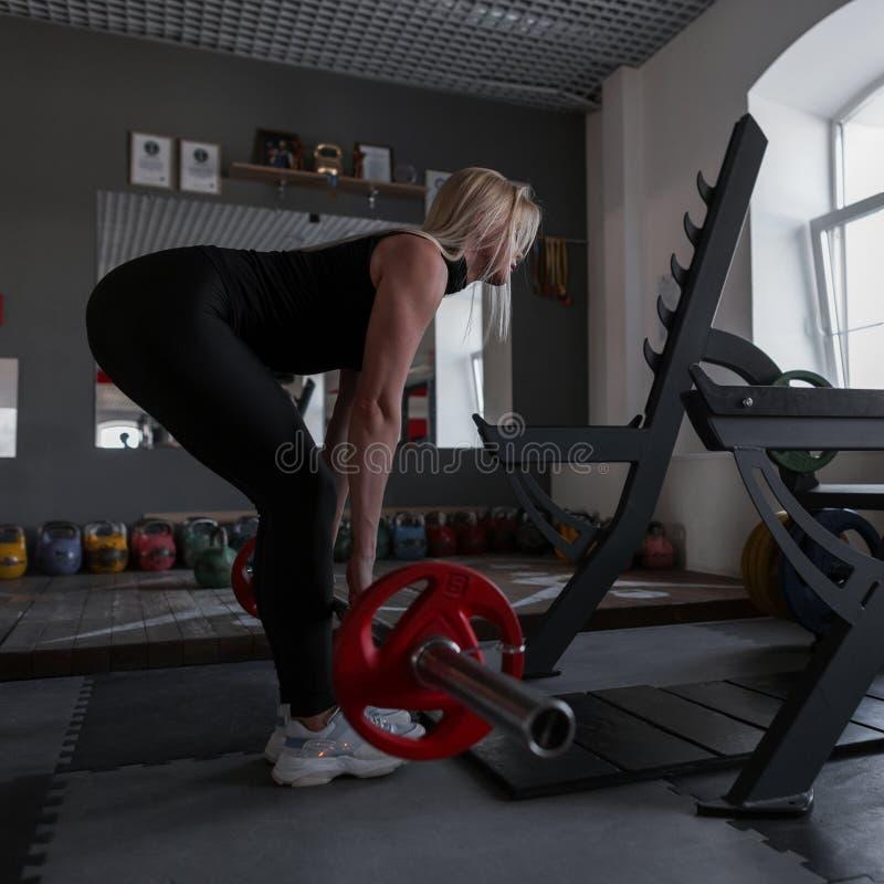 La giovane donna perfetta con un corpo sportivo sta facendo gli esercizi con un bilanciere nella palestra Treni della ragazza con fotografia stock libera da diritti