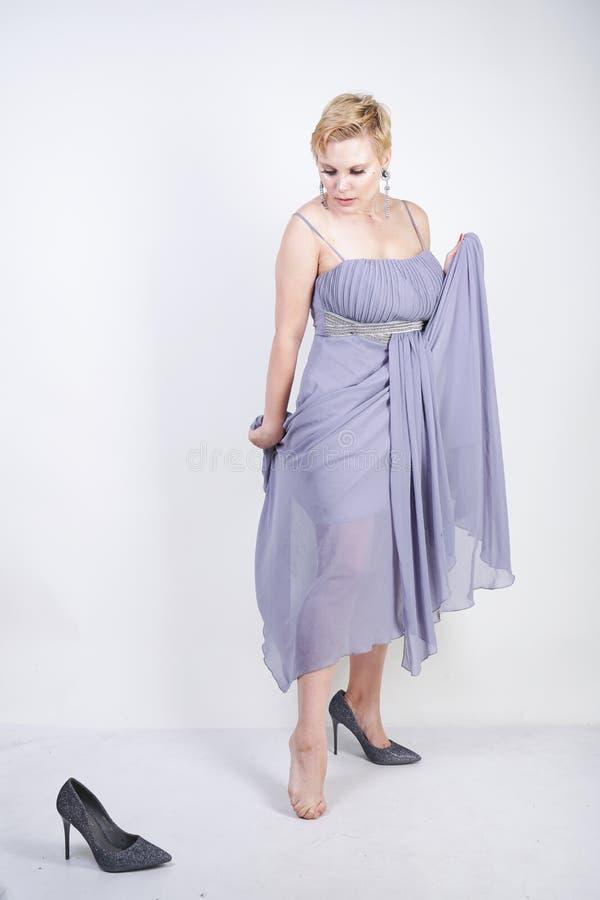 La giovane donna più incantante di dimensione in vestito grigio dall'abito ha perso la pantofola su fondo bianco in studio bella  fotografie stock