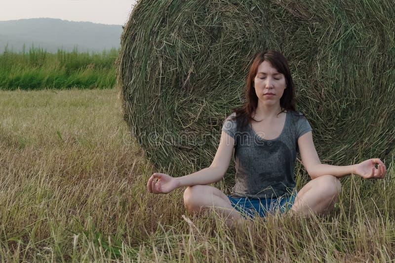 La giovane donna pratica la meditazione sulla balla di fieno del fondo immagini stock libere da diritti