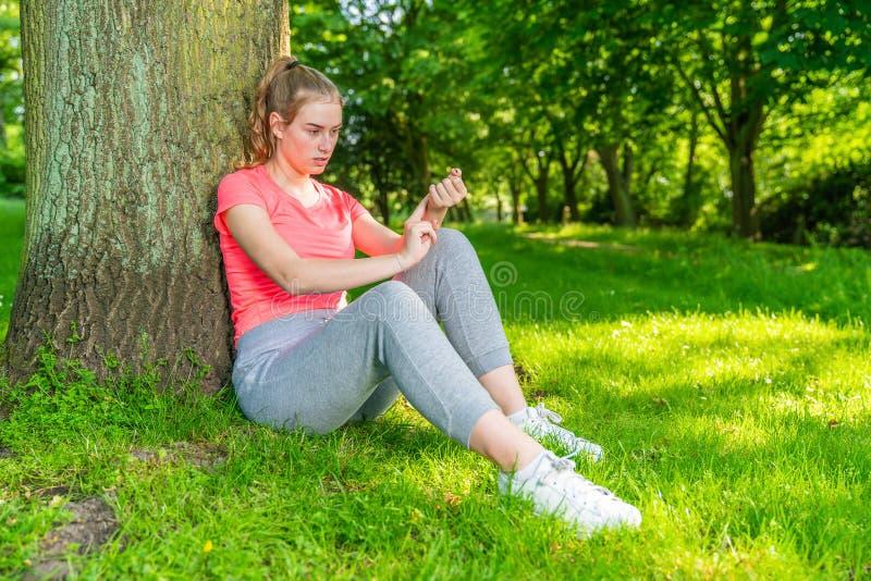 La giovane donna prende una rottura durante lo sport e le misure i suoi puls fotografia stock