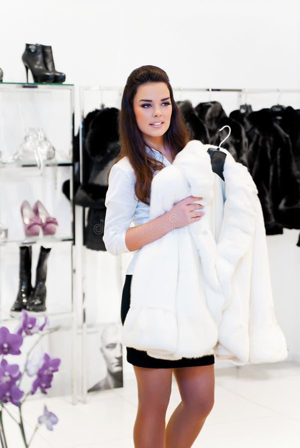 La giovane donna prova sopra un cappotto di pelliccia fotografia stock libera da diritti