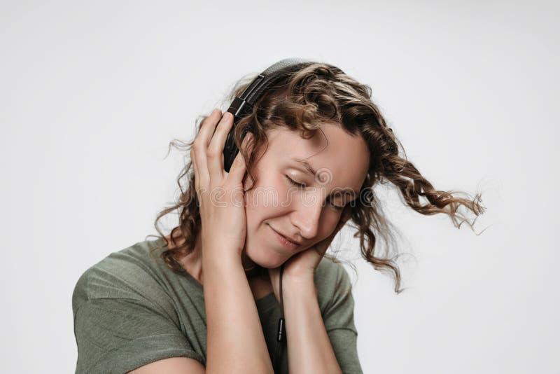 La giovane donna riccia allegra spensierata ascolta musica favorita con la mano sulle sue cuffie immagini stock