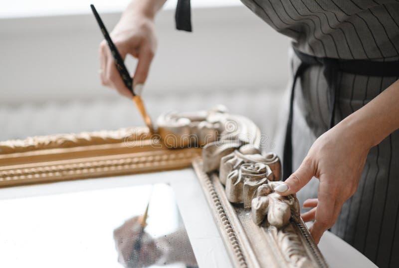 La giovane donna ripara la struttura per uno specchio o un'immagine fotografie stock libere da diritti