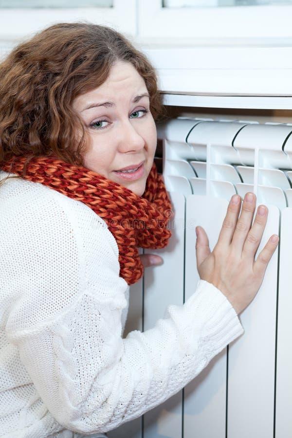 La giovane donna ritiene il freddo sedersi vicino al raggiro del riscaldamento fotografie stock
