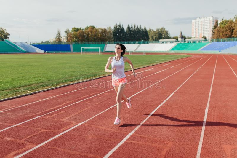 La giovane donna in rosa mette e carro armato ad correre nel corso della mattinata soleggiata sulla pista dello stadio fotografia stock libera da diritti