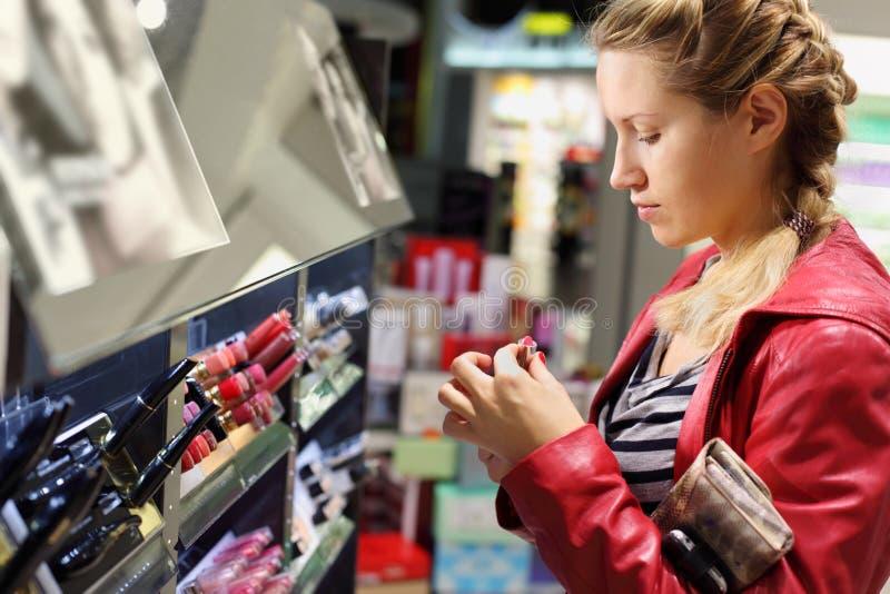 La giovane donna sceglie il rossetto in negozio. fotografia stock libera da diritti