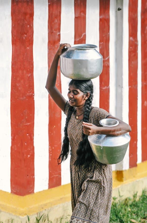 La giovane donna sconosciuta porta il contenitore dell'acqua indietro dalla comunità immagine stock