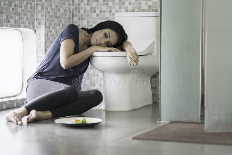 La giovane donna sembra stanca dopo il vomito immagini stock