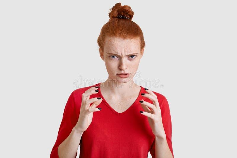 La giovane donna sexy dispiaciuta ha pelle freckled, tiene le mani nel gesto arrabbiato, guarda con rabbia, indossa i vestiti ros fotografie stock libere da diritti