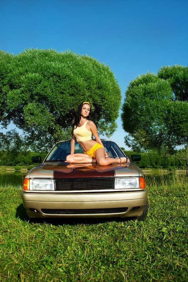 La giovane donna sexy si siede sulla retro automobile immagine stock libera da diritti