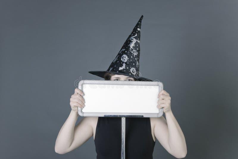 La giovane donna si è vestita in abito nero e cappello del pellegrino che tengono un segno bianco in bianco normale su fondo grig immagini stock libere da diritti