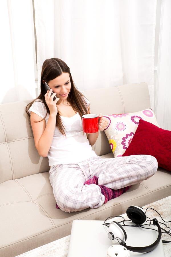 La giovane donna si rilassa a casa la conversazione dal telefono fotografia stock libera da diritti