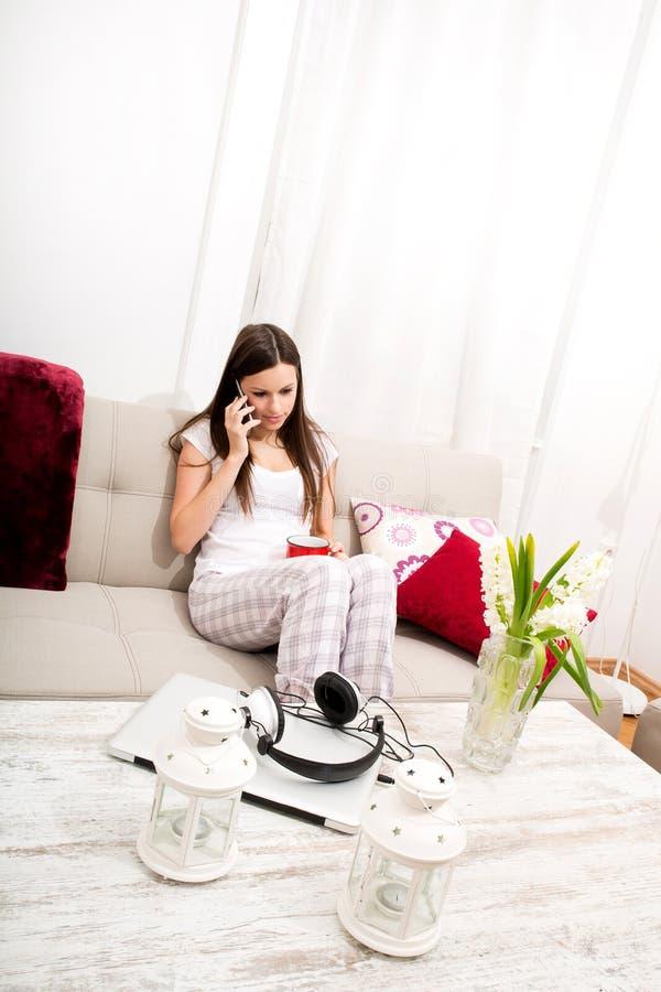 La giovane donna si rilassa a casa la conversazione dal telefono immagini stock libere da diritti