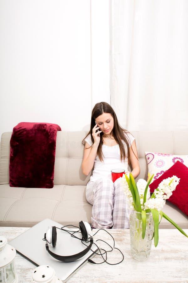 La giovane donna si rilassa a casa la conversazione dal telefono fotografie stock