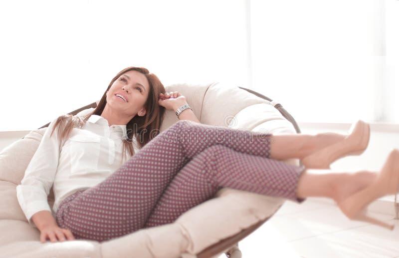 La giovane donna si rilassa in una sedia comoda fotografie stock
