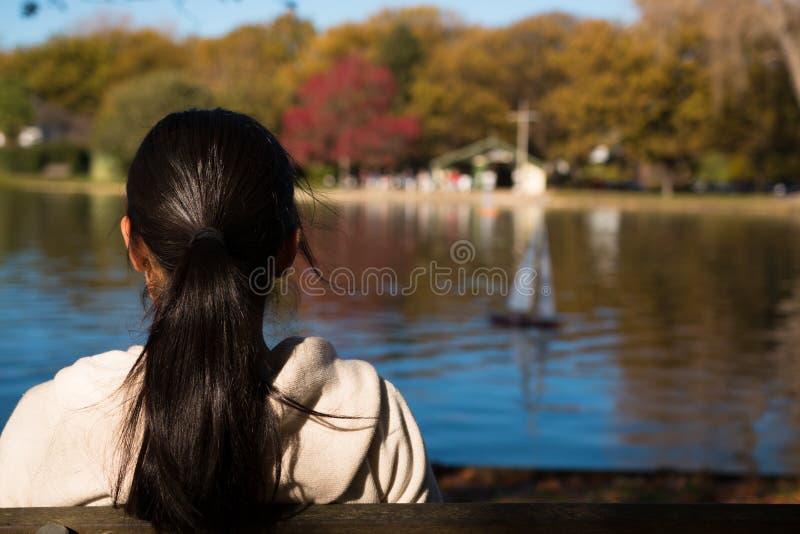 La giovane donna si siede ed esamina l'yacht di modello su un lago immagini stock