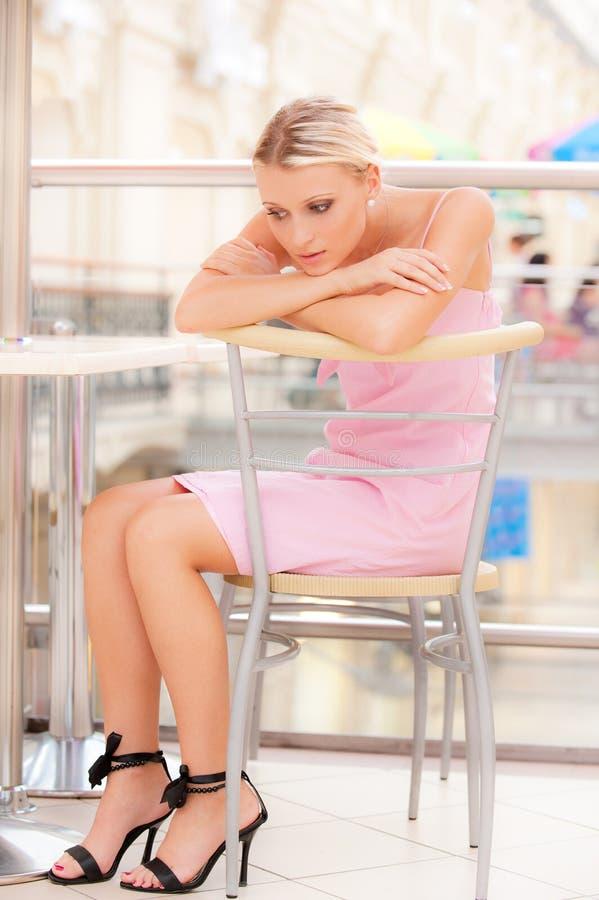 La giovane donna si siede a poca tabella al ristorante fotografia stock libera da diritti