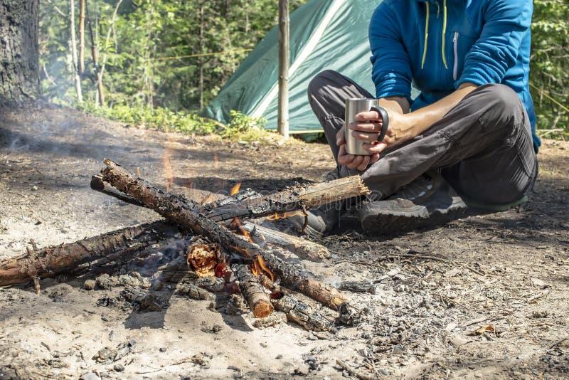 La giovane donna si siede rilassato sulla terra con le sue gambe ha attraversato, dal fuoco, in sue mani che tiene una tazza con  fotografia stock