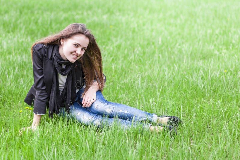 La giovane donna si siede su prato inglese immagine stock