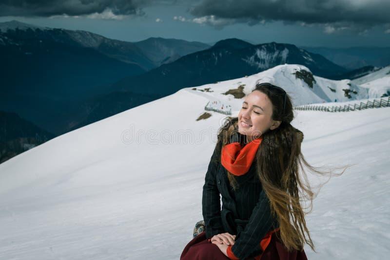 La giovane donna si siede sulla cima delle montagne nevose nella stazione sciistica fotografia stock libera da diritti