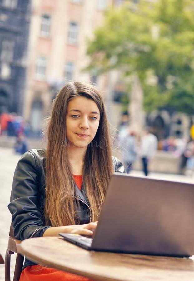 La giovane donna si siede sulla tavola di legno che lavora al computer immagini stock libere da diritti