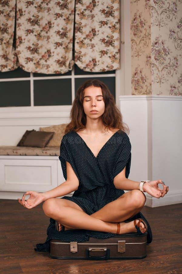 La giovane donna si siede in una posa di yoga sulla valigia fotografia stock libera da diritti