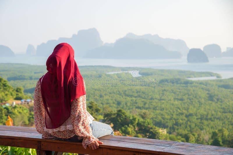 La giovane donna siede e vede la montagna la mattina presto al punto di vista dell'isola di Sametnangshe, Phang-Nga, Thailandia W fotografia stock