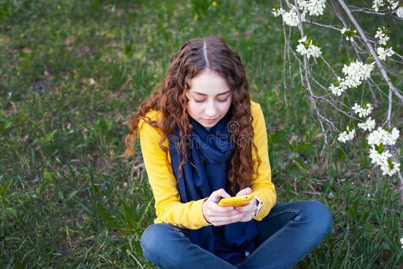 La giovane donna smilling che si siede in un giardino di fioritura e scrive sul telefono cellulare Ciliegia di fioritura Ritratto immagini stock