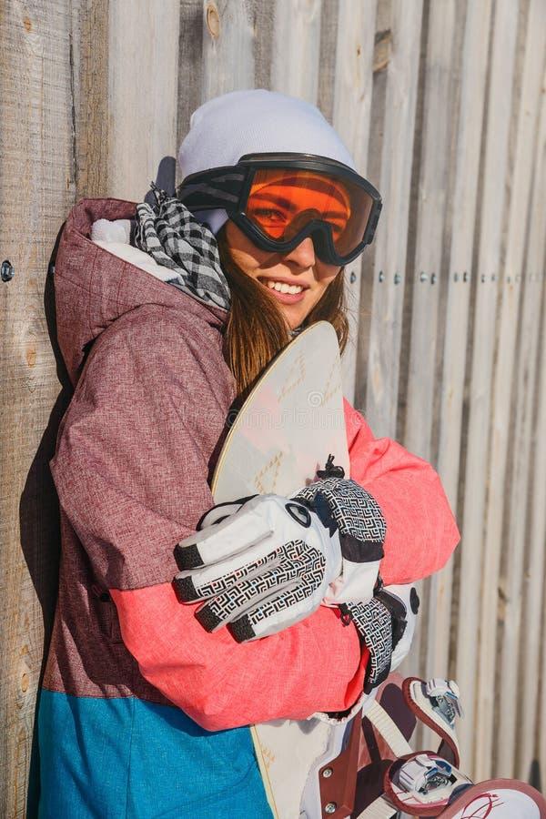 La giovane donna sorridente abbraccia lo snowboard fotografie stock libere da diritti