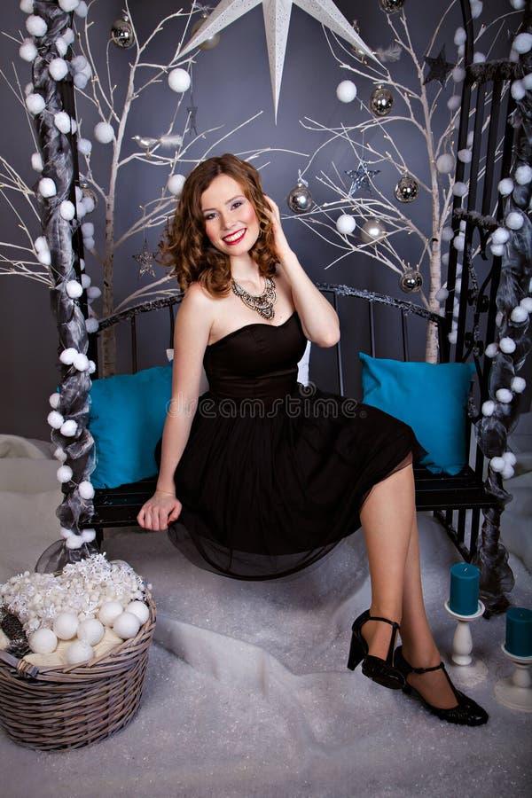 La giovane donna sorridente che si siede sul Natale dell'inverno bench immagine stock libera da diritti