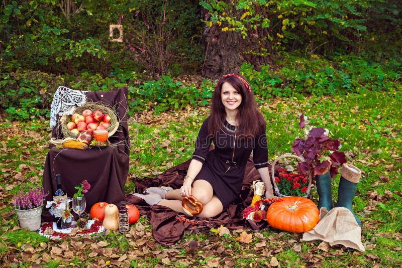 La giovane donna sorridente che si siede vicino alle verdure in autunno parcheggia fotografia stock