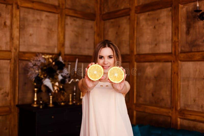 La giovane donna sorridente di venti anni mostra due metà dell'arancia immagini stock libere da diritti