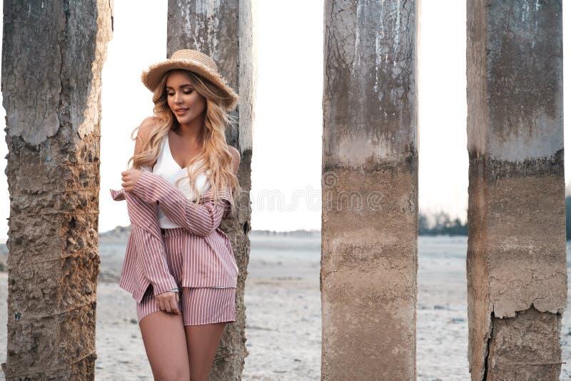 La giovane donna sorridente elegante, alla moda e delicata con capelli biondi sciolti lunghi in un cappello di paglia gode della  fotografia stock libera da diritti