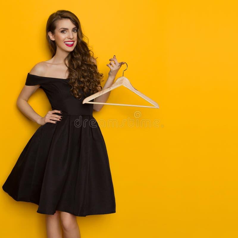 La giovane donna sorridente elegante sta tenendo il gancio fotografie stock libere da diritti